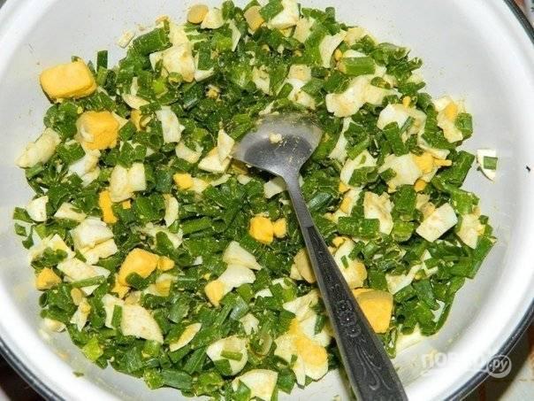 3. Яйца отвариваю и остужаю, затем нарезаю кубиками. Зеленый лук мою и измельчаю, смешиваю яйца с луком, по вкусу солю.