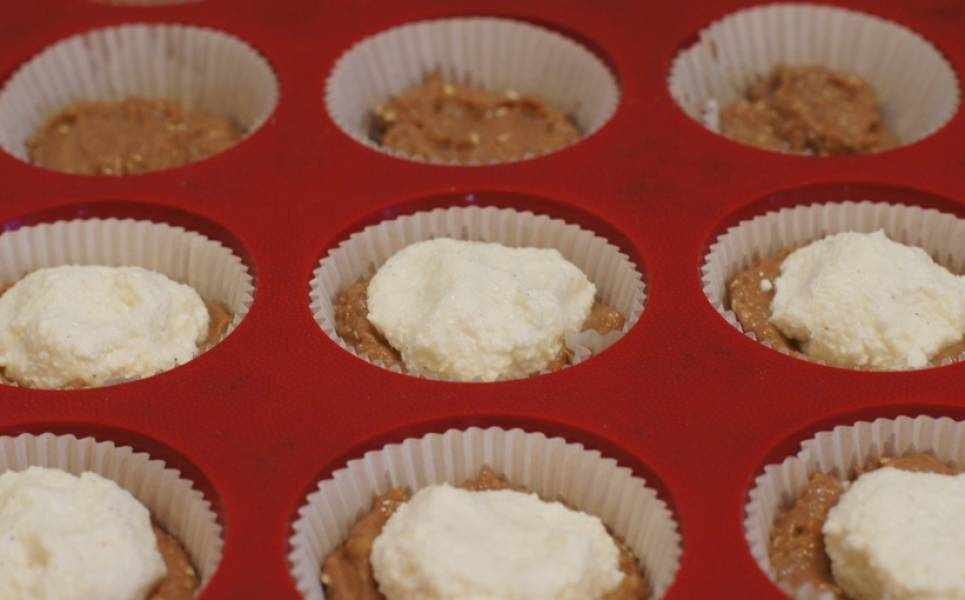 Разделите тесто на две части. Форму застелите бумагой для выпечки кексов. Каждую ложбинку наполовину заполняем тестом. Сверху раскладываем творожную начинку (творог, смешанный с сахаром и с ванильным сахаром).