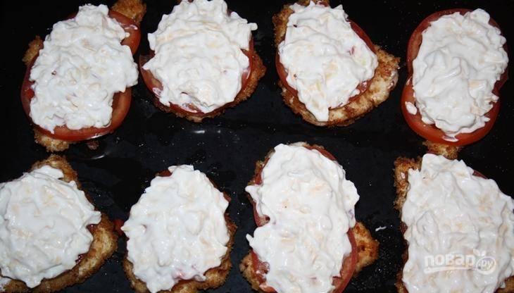 При помощи ложки выложите сырно-майонезную массу на каждый кусочек курицы с овощами. Затем разогрейте до 200 градусов духовку, поставьте в нее противень с блюдом. Запекайте 10 минут. Приятного аппетита!