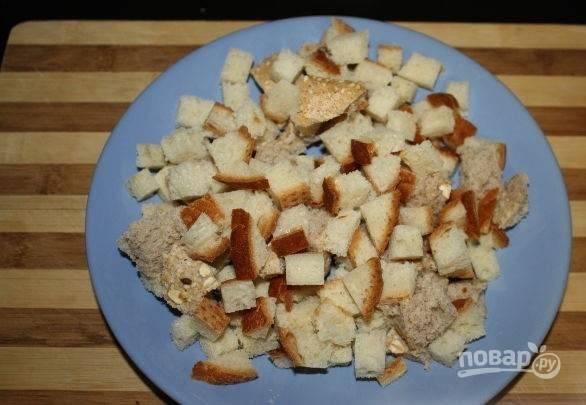 2. Хлеб нарежьте небольшими кубиками. Добавьте соль, специи и немного оливкового масла. Перемешайте.