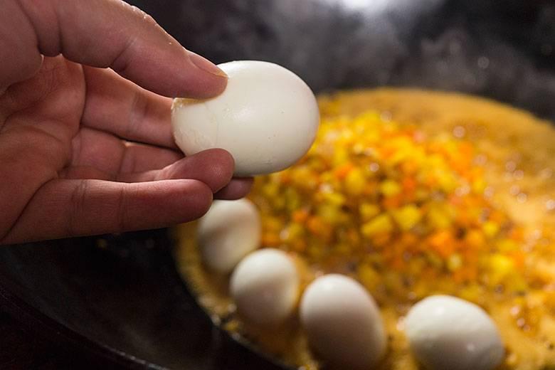 10. Когда морковь кубиками обжарится, добавить специи и выложить в казан очищенные яйца.