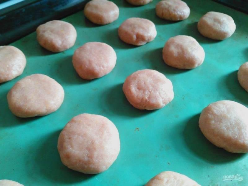 Отщипывайте кусочки теста, формируйте из них шарики размером с грецкий орех. Поместите шарики на противень и слегка придавите рукой.