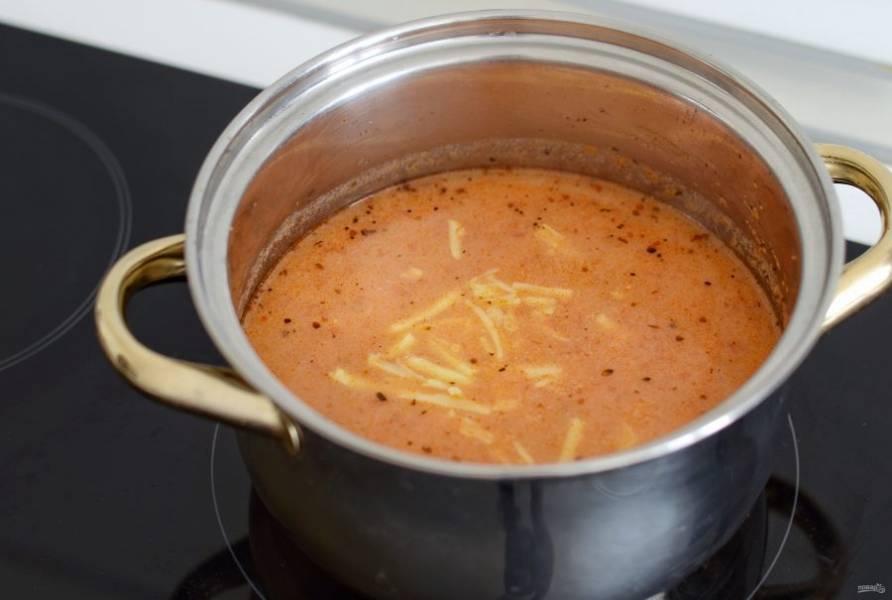 В конце влейте молоко, перемешайте. Сыр натрите на крупной терке, добавьте в кастрюлю. Варите суп на среднем огне, пока сыр не растворится.