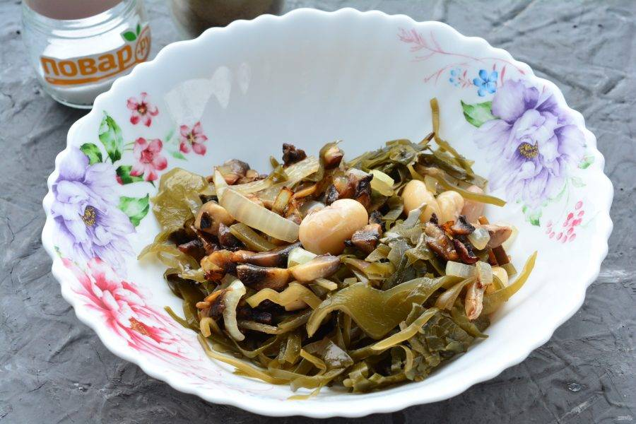 Выложите в миску морскую капусту, жареные грибы и добавьте консервированную белую фасоль.