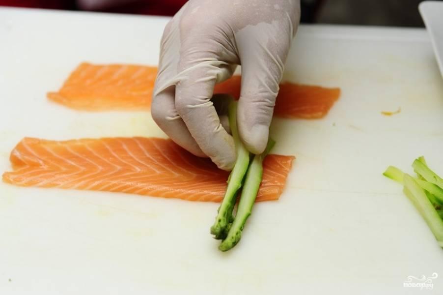 На тонкие пластины лосося выкладываем спаржу.