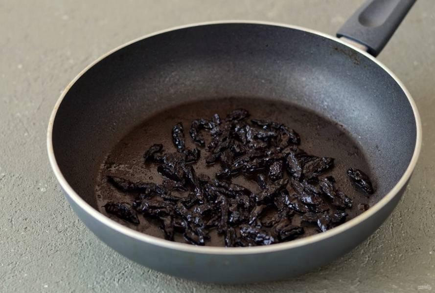 Чернослив нарежьте соломкой. Обжарьте в растительном масле 1-2 минуты. Затем добавьте к черносливу соевый соус. Перемешайте, обжаривайте ещё 1-2 минуты.