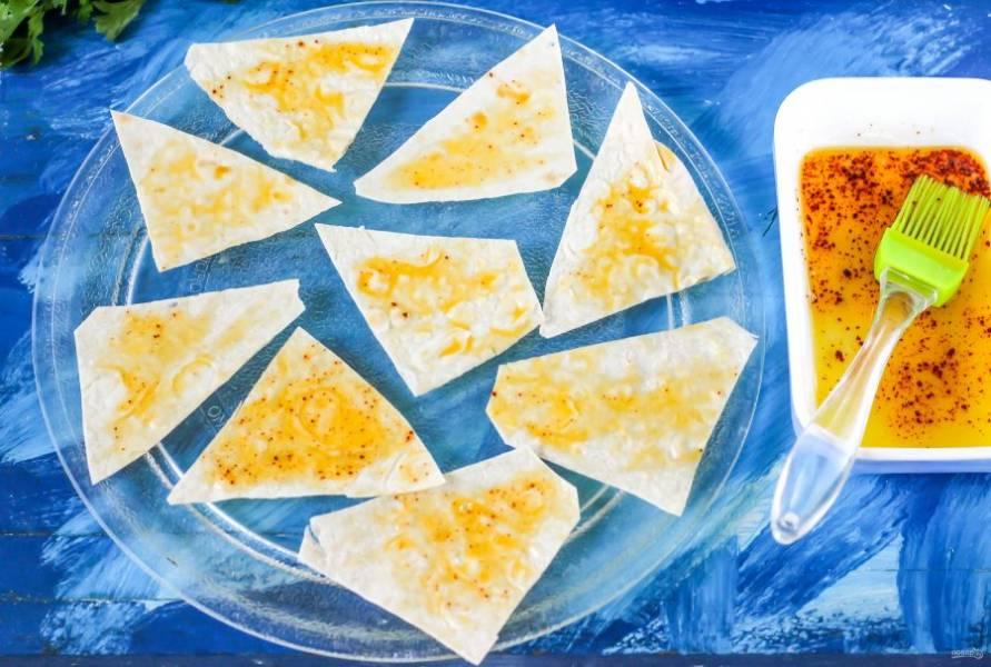 В пиале соедините растительное масло, соль, молотую паприку и молотый сушеный чеснок. Аккуратно перемешайте. Кулинарной кисточкой слегка смажьте нарезку лаваша сверху. Но только слегка, чтобы тесто не вобрало в себя масло. Разложите треугольники на поддоне и поместите в микроволновку буквально на 1 минуту.
