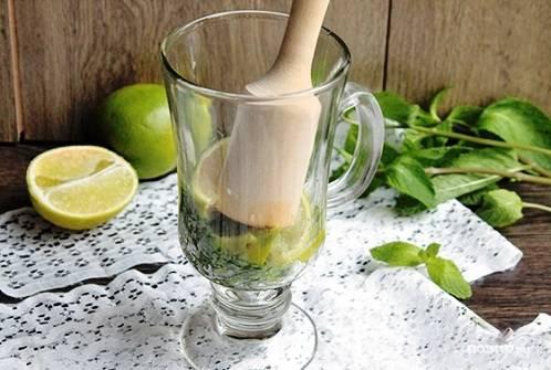 Дальше в бокал отправляем лайм, разминаем его пестиком до появления сока.