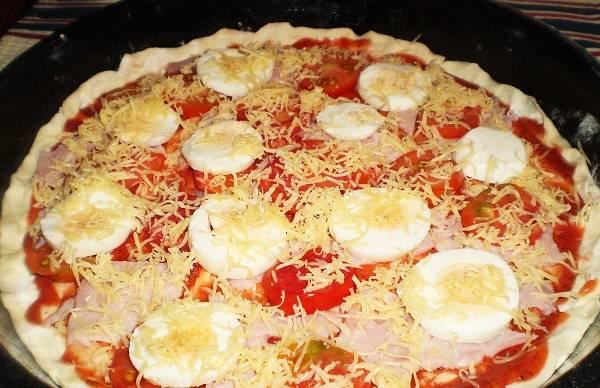 8. Яйца нарезать кружочками и выложить на тесто, присыпать все тертым сыром и отправить в разогретую духовку. Как только сыр расплавится, а корж подрумянится - пиццу можно доставать и подавать к столу.