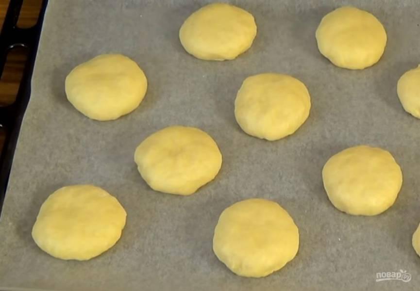 1. Половину порции сдобного теста на сметане скатайте в жгут и разделите на 10 одинаковых частей. Каждую часть соберите в узелок и выложите на бумагу для выпечки собранной стороной вниз.