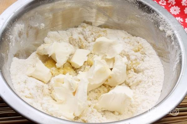 Затем добавьте слегка мягкое масло. Замешайте тесто.