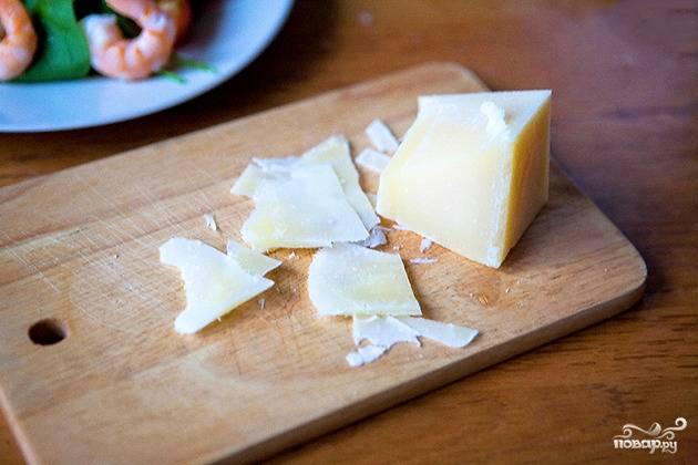 Через 3-4 минуты креветки будут готовы. Смешиваем их с салатной основой и орешками. Тонко нарезаем сыр и украшаем им салат.