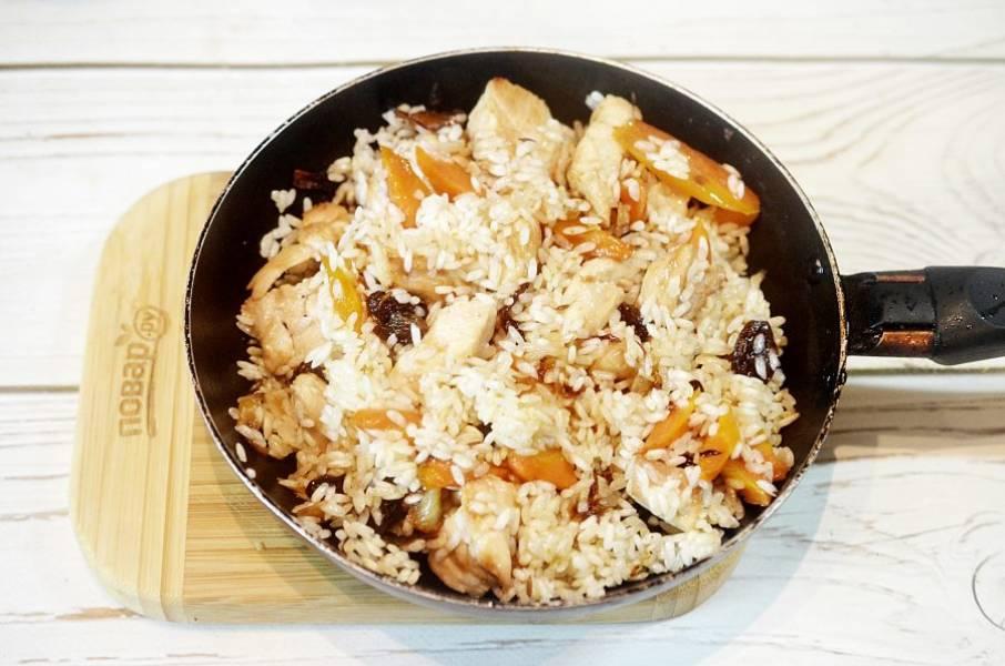 8. Рис очень хорошо промойте и добавьте в сковороду. Обжарьте рис на сковороде, чтобы каждая рисинка впитала в себя масло, - тогда плов получится рассыпчатый.
