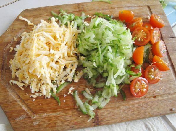 Натрите на терке сыр, помидоры и огурцы мелко порежьте.