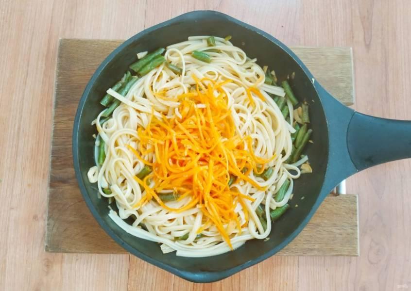 В пасту добавьте морковку по-корейски, рыбный соус и соевой соус. Хорошо перемешайте и протомите пару минут.