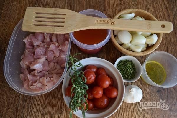 Подготовьте необходимые продукты. Куриное мясо порежьте на кубики, поперчите и посолите по вкусу, полейте оливковым маслом. Лук, чеснок очистите.