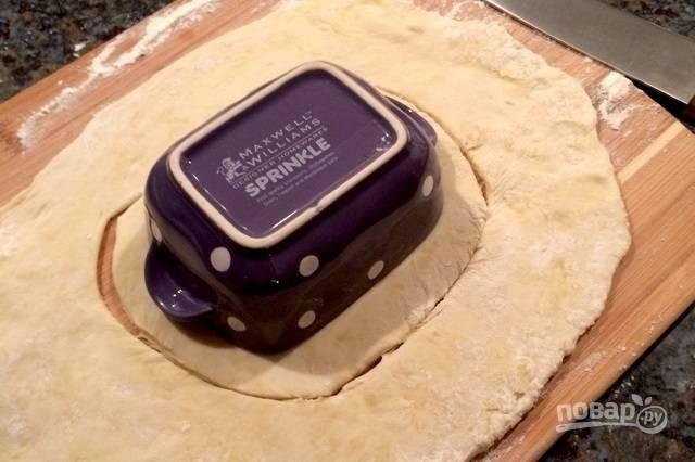 """9.Посыпьте столешницу мукой и выложите тесто, раскатайте его в пласт, но не очень тонкий. Уложите горшочек и вырежьте по форме немного больше него, чтобы можно было сделать для него """"крышку""""."""
