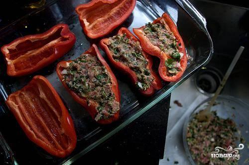 2. Выложить половинки болгарского перца в форму для выпечки. Заполнить каждый перец мясной начинкой.