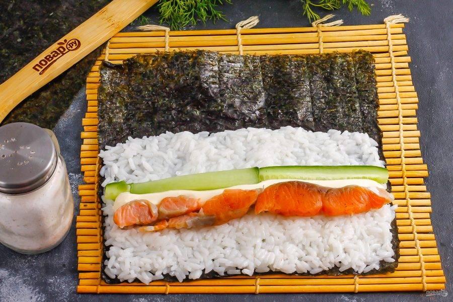 На рис выложите сливочный сыр и ломтики слабосоленой семги или лосося. Нарежьте промытый огурец длинными ломтиками и добавьте к остальной начинке.