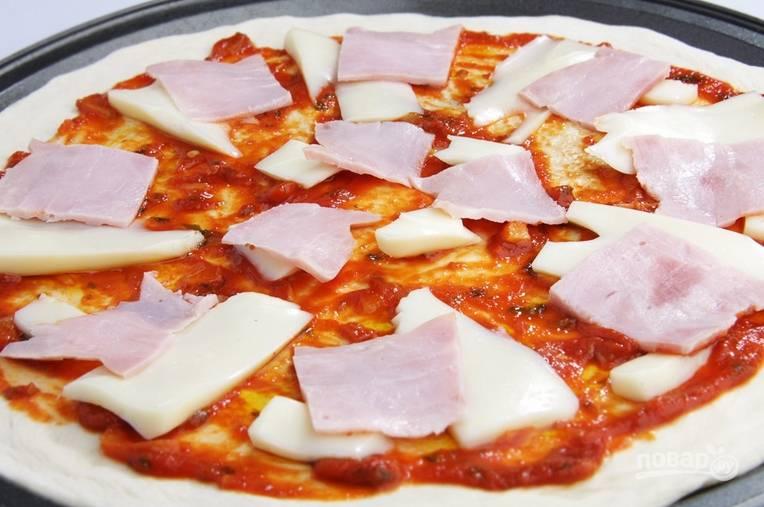Тонкими ломтиками нарежьте ветчину и моцареллу. Разложите ингредиенты по всей пицце.
