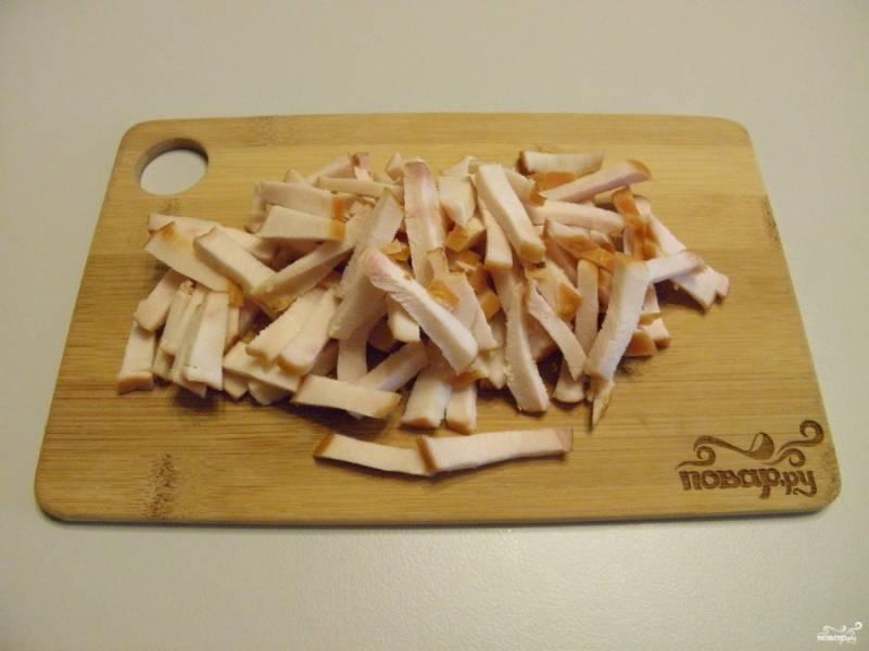 Копченое куриное мясо порежьте соломкой.