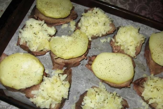Застилаем противень бумагой для выпечки, выкладываем на него ломтики свиного языка. Солим и перчим мясо, а сверху кладем картофель, порезанный пластинками.