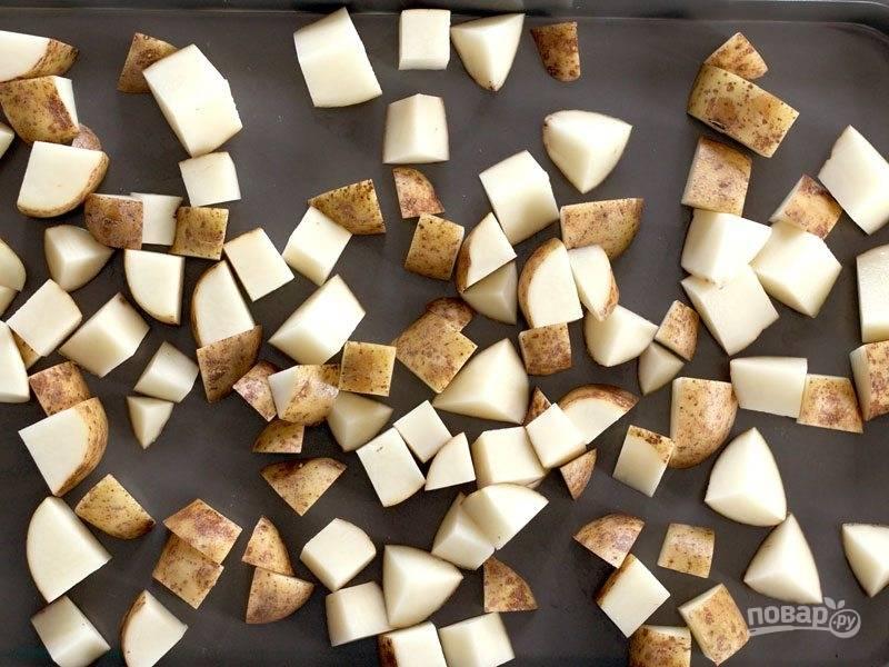 Картофель хорошо помойте и порежьте средним кубиком. Уложите в противень.