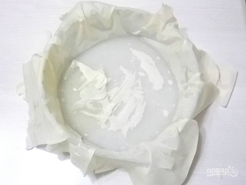 Смажьте форму маслом и уложите размороженный лист теста, чтобы свисали края.