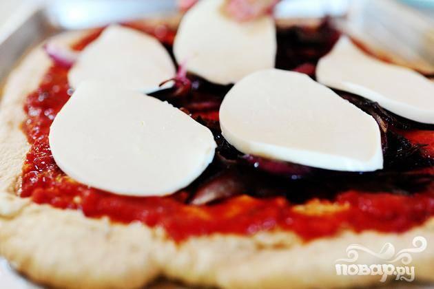 5. Выложить красный лук сверху, а затем тонко нарезанные ломтики сыра Моцарелла. Выпекать пиццу в течение 12-15 минут, до золотистой корочки, пока сыр не начнет бурлить.
