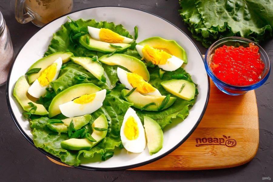 Разрежьте авокадо пополам, очистите от кожуры и удалите ядро. Нарежьте мякоть ломтиками и выложите на тарелку. Промойте зеленый лук и измельчите, присыпьте им сверху нарезки яйца и авокадо.