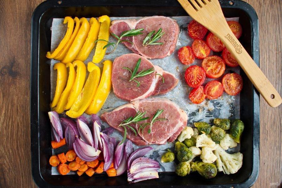 Отодвиньте овощи в строну. В центр положите стейки, посолите, поперчите, полейте оливковым маслом, сверху положите веточку розмарина. Поставьте запекаться на 15 минут.