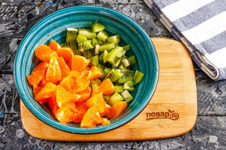 Очистите мандарин от кожуры, разделите плод на дольки и удалите белые нити и косточки, если такие присутствуют. Киви очистите от кожуры, промойте и нарежьте средними кубиками, как и мандарин. Высыпьте нарезки в глубокую емкость.