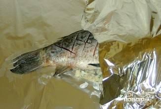 5.Рыбу фаршируем начинкой. Фольгу смазываем рафинированным масло, плотно оборачиваем ею рыбу.