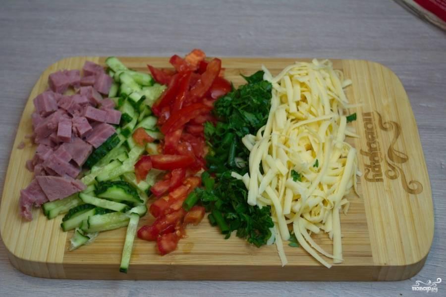 Натрите на терке твердый сыр. Измельчите зелень и нарежьте кубиками колбасу или ветчину. Лучше использовать ветчину. Она сочная.