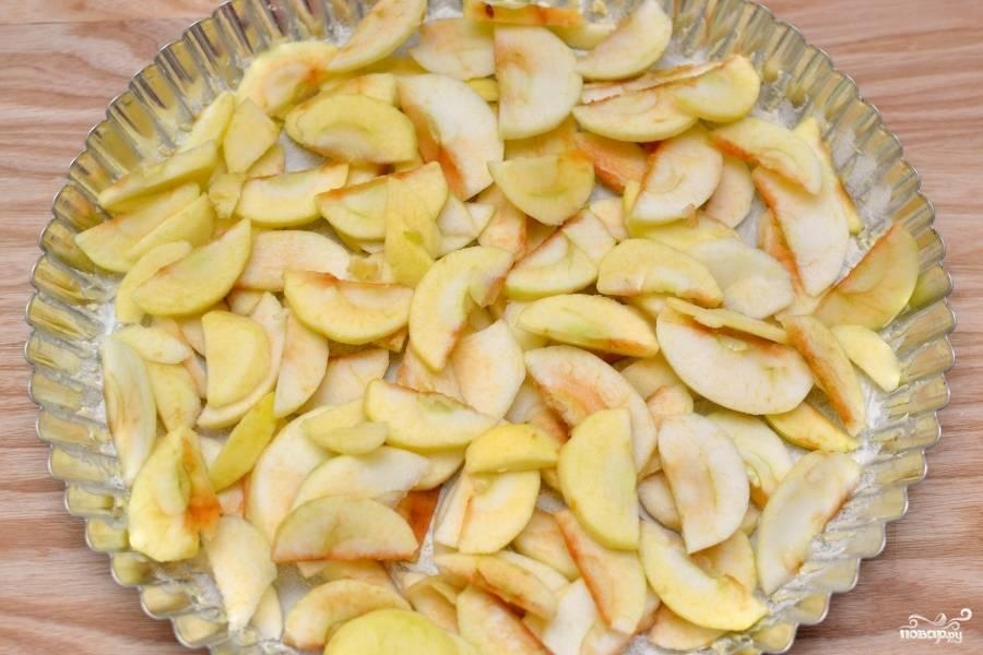 Почистите яблоки от кожуры. Разрежьте на тонкие дольки. Форму для выпекания пирога смажьте растительным маслом или покройте пекарской бумагой. Выложите яблоки.