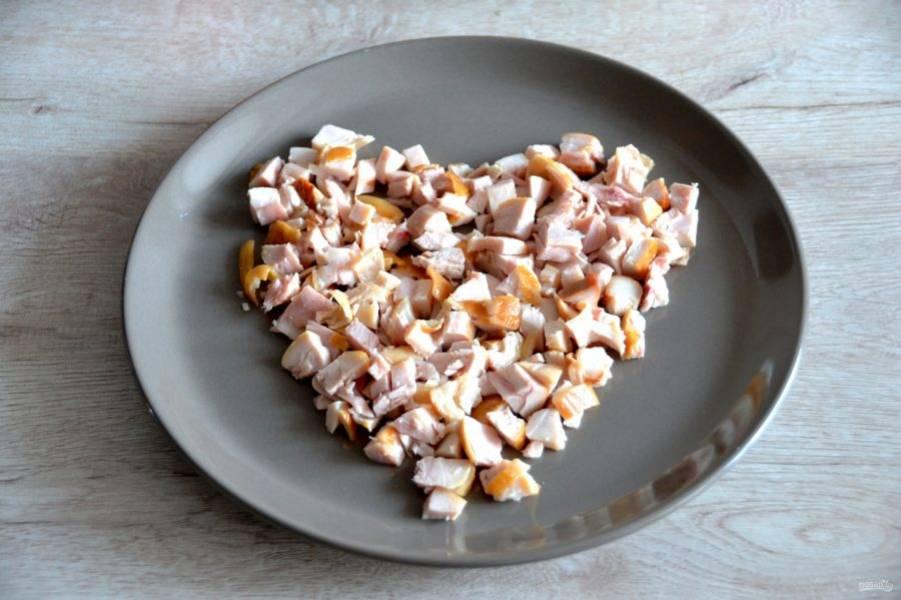 """Выкладывайте салат сразу на большой тарелке в форме """"сердца"""". Нарежьте кубиком копченую курицу и выложите первый слой."""