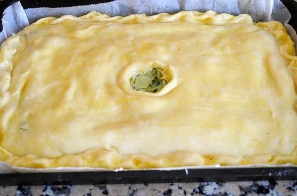 6. Накройте вторым листом теста, хорошо завернув края. Чтобы нежный пирог с капустой в домашних условиях не был внутри влажным, сверху нужно сделать небольшое отверстие для выхода пара. Смажьте верх пирога взбитым желтком.