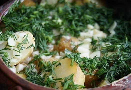 Вынуть картофель из духовки, удалить тимьян. Посыпать чесноком и зеленью.