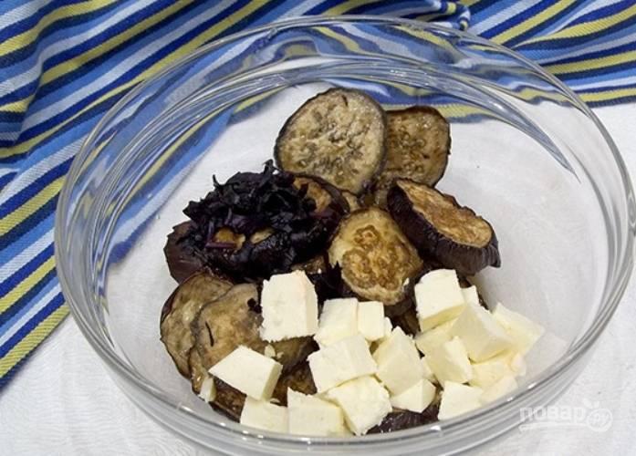 Выкладываем запеченные баклажаны в салатницу, добавляем сыр.