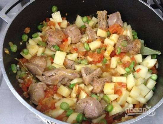 Перекладываем содержимое сковороды к кролику, добавим фасоль и горошек. Очистим картофель, нарежем его, как вам нравится, но не очень мелко. Добавим соль, перец, лавровый лист. Наливаем примерно полтора стакана воды. Накрываем крышкой и ставим в разогретую до 200 градусов духовку.