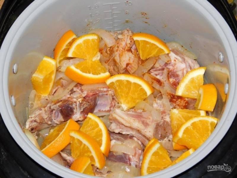 """Выложите куски баранины. Добавьте нарезанные апельсины. Подлейте немного воды и включите режим """"Тушение"""" на 1,5 часа."""
