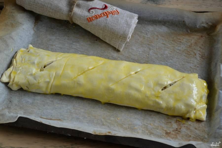 Заверните тесто в рулет, защипните края. Сверху сделайте несколько неглубоких надрезов. Смажьте штрудель взбитым яйцом, отправьте его в духовку, разогретую до 180 градусов, на 15 минут.