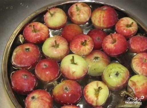 Промываем яблоки. Вываливаем их в таз и заливаем водой. Там отмачиваем и отмываем. Далее нарезаем яблочки на кусочки. Огрызки не выкидываем. Их также можно класть в компот. Получается еще насыщеннее. К тому же яблочные косточки безумно полезны!