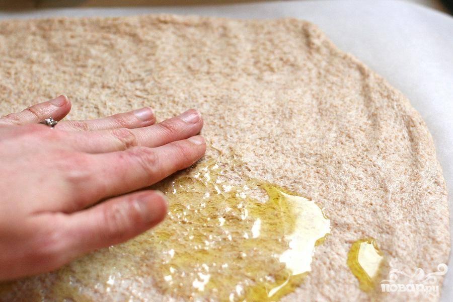 1. Предварительно разогреть духовку до 230 градусов. Раскатать готовое тесто для пиццы на пергаментной бумаге в большой круг 30-40 см в диаметре и выложить его на противень. Полить тонкой струйкой оливкового масла. Равномерно распределить масло по поверхности теста руками.