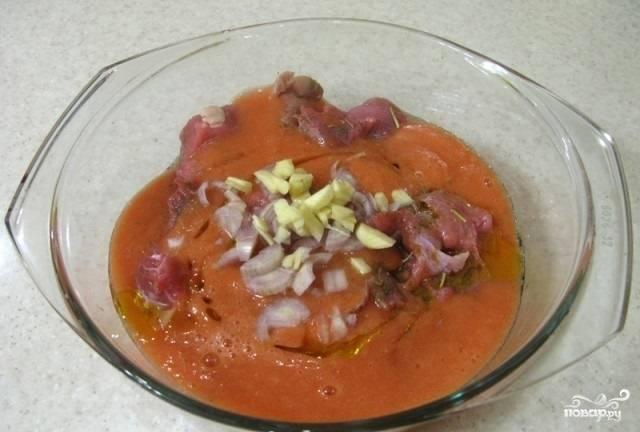 3.Помидоры бланшируем и нарезаем кусочками, отправляем в миску. Погружным блендером разминаем их в пюре. Заливаем полученной массой мясо в миске. Нарезаем лук и чеснок, также добавляем их к мясу, вливаем оливковое масло.
