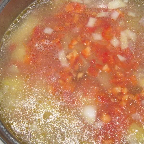 3. В последнюю очередь добавим мелко порезанный перец и помидор, перетертый в пюре. Чеснок пропустим через пресс и тоже отправим в кастрюлю. Специи - по вкусу. Как только снова закипит, кладем мелкую вермишель и выключаем огонь.