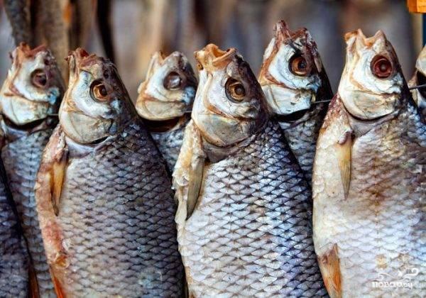 3.Дайте рыбе стечь. Промокните бумажным полотенцем. Нанижите на леску, проволоку или толстую нитку через глаза и жабры рыбу. Сушите а проветриваемом помещении от 3 до 7 дней в защищенном от прямых солнечных лучей помещении в развешенном состоянии. Сверху прикройте марлей от мух. Готовность проверяйте по твердости продукта. Храните в полиэтиленовых пакетах в морозилке.