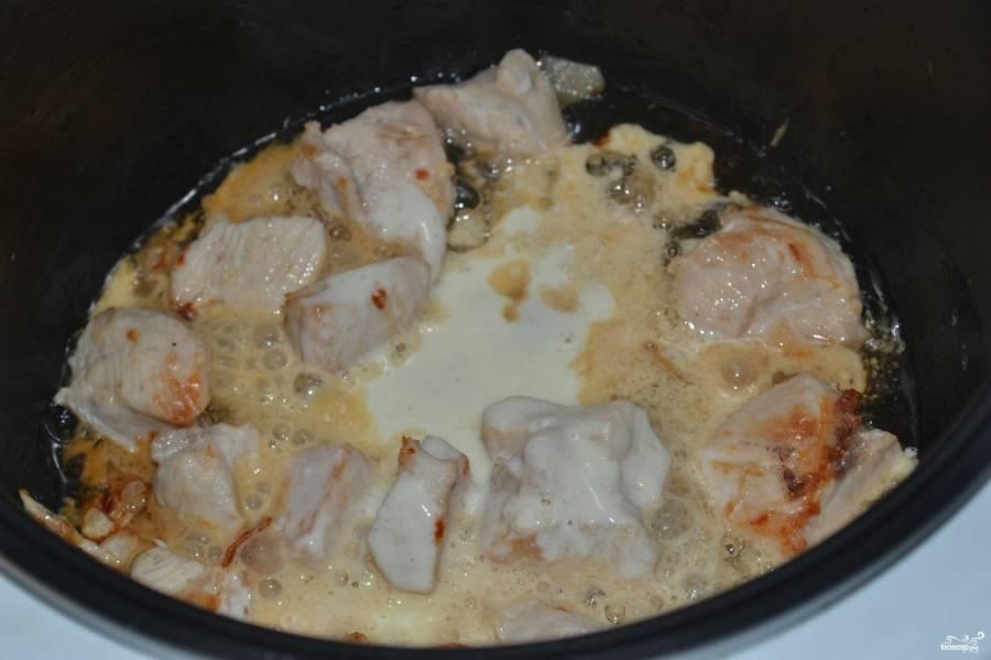 """В чашу мультиварки выложите порезанное мясо, добавьте масло, какое вы больше любите. Поставьте режим """"Жарка"""" на 10 минут. По окончании времени положите чеснок, все посолите и залейте сметаной. Включите режим """"Тушение"""" и готовьте еще 30 минут. После сигнала об окончании готовки оставьте тушеную курочку примерно на 20 минут, чтобы она хорошо набралась ароматов подливки."""