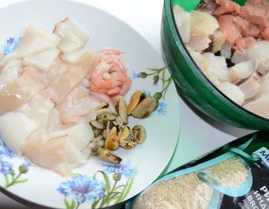 Если вы используете замороженную рыбу, то дайте ей предварительно оттаять. Затем зачистите филе от косточек, которые могут в нем быть. Нарежьте на крупные куски рыбу, креветки освободите от панциря, кальмары почистите и также нарубите на куски.