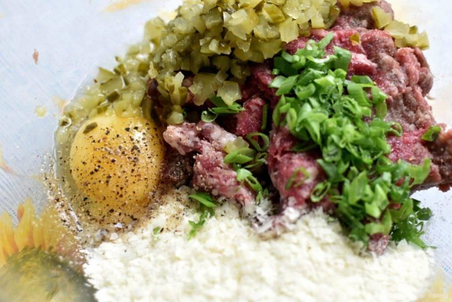 Смешайте фарш с мелко нарубленными огурчиками, картофельными хлопьями и рубленым зеленым луком. Добавьте яйцо, посолите и поперчите по вкусу.